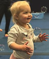 Toddler playing smiling at bubbles